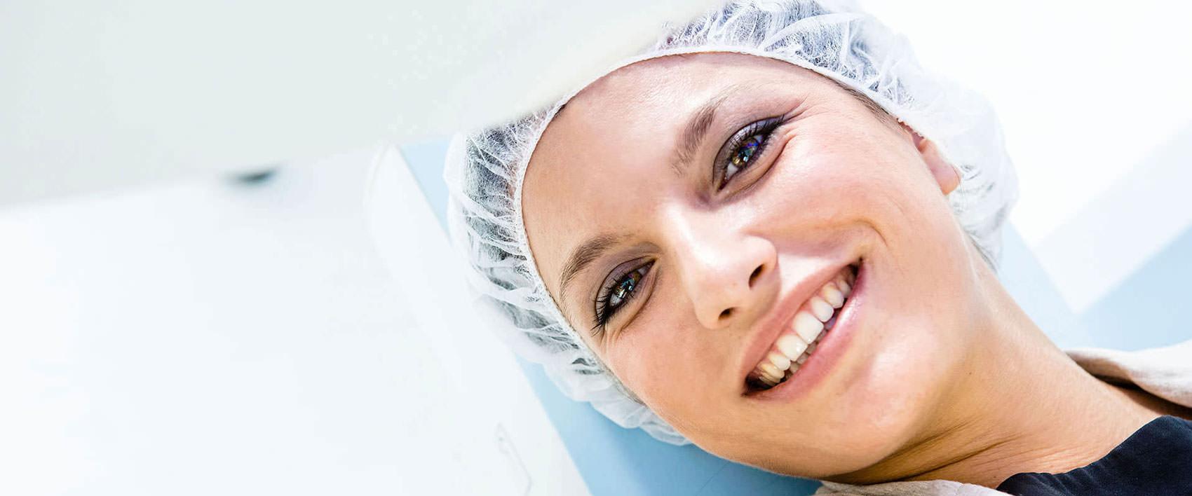 In die Kamera lächelnde Patientin mit Hygienehaube