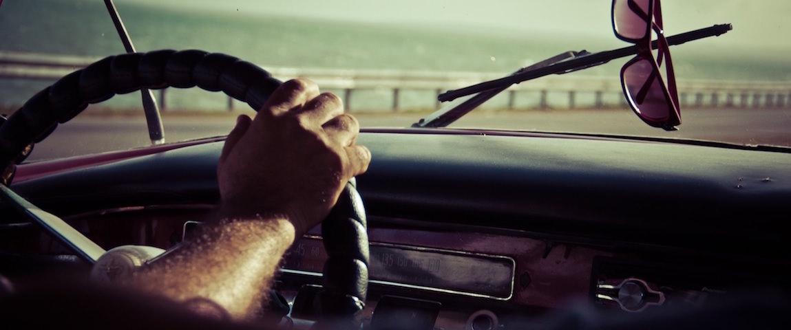 Bilk aus einem Auto durch die Frontscheibe. Hand von Fahrer zu sehen und Sonnenbrille, die von oben herunterhängt.