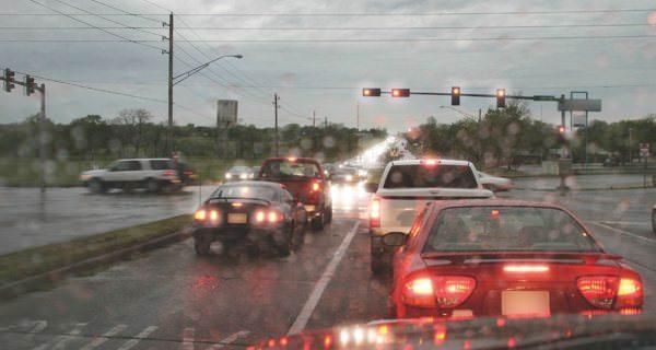 Dichter Straßenverkehr im Ampelbereich aus Fahrersicht bei regnerischem Wetter und nasser Windschutzscheibe