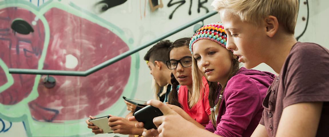 Schüler nebeneinander sitzend mit Smartphones in der Hand