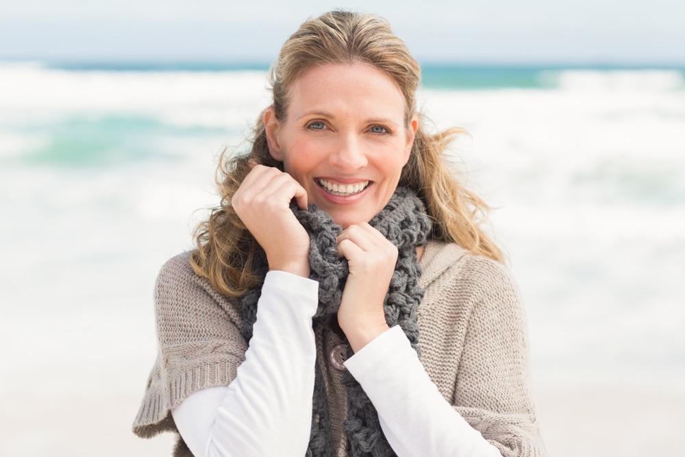 Frau mittleren Alters steht am Strand mit dem Rücken zum Meer und blickt in die Kamera.