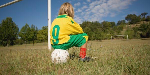 Teaser: Junge sitzt auf einem Fußball.