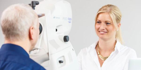 Assistentin untersucht einen Patienten am OCT.