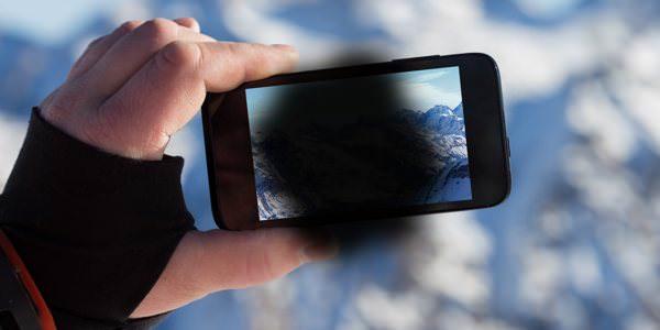 Hand hält ein Smartphone. Im Zentrum des Motivs ist ein schwarzer Fleck.