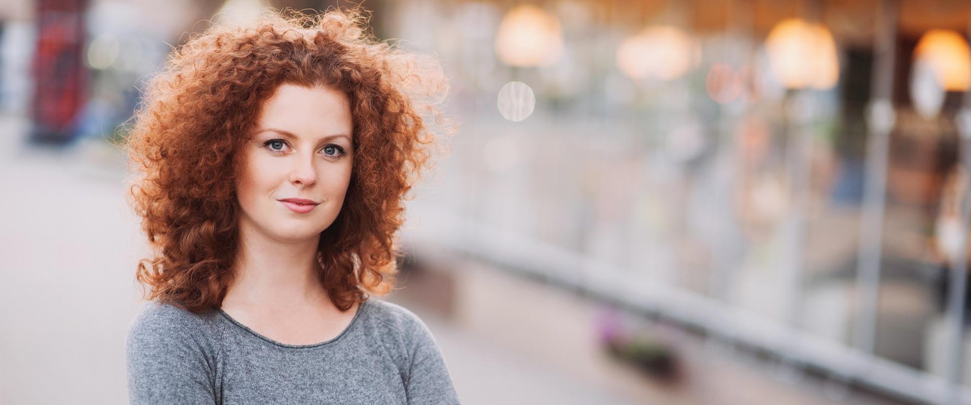 Junge Frau mit roten lockigen Haaren blickt in die Kamera.