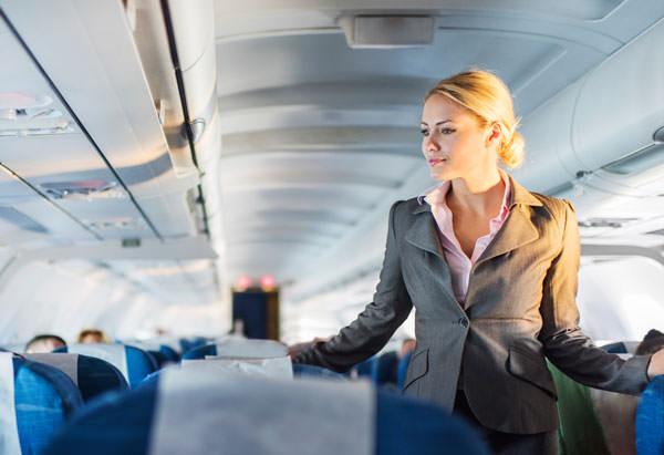 Stewardessen im Gang zwischen den Sitzreihen eines Flugzeugs