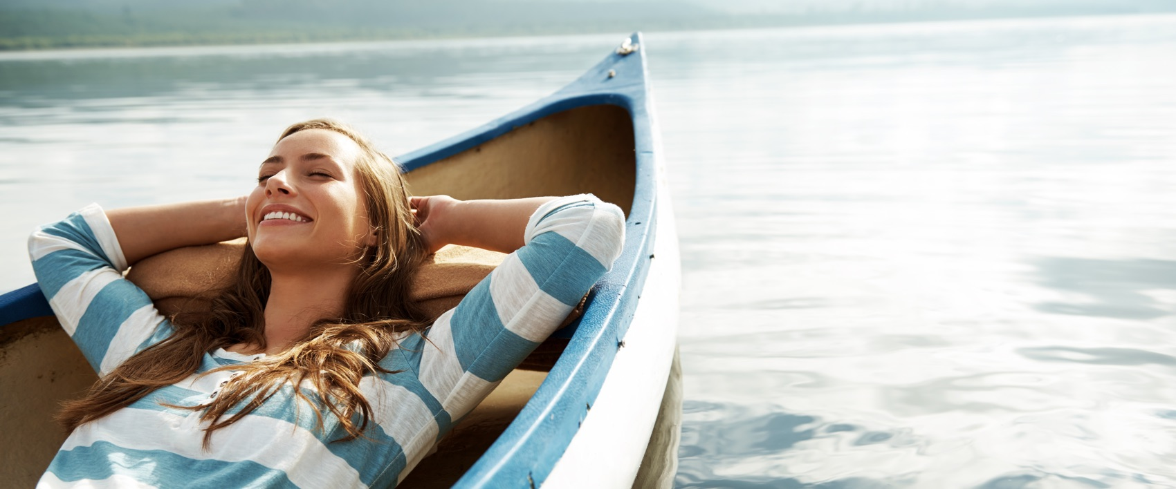 Junge Frau liegt entspannt in einem Boot auf dem Wasser.