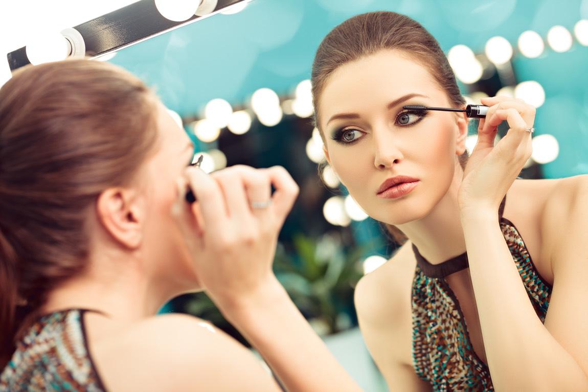 Elegante Frau im Partyoutfit steht vor einem Spiegel und trägt Augen-Make-up auf.
