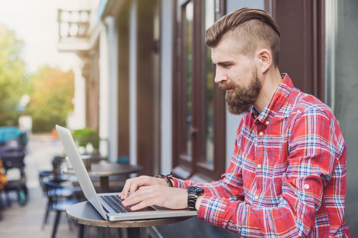 Junger Mann mit Bart in einem Café am Laptop.