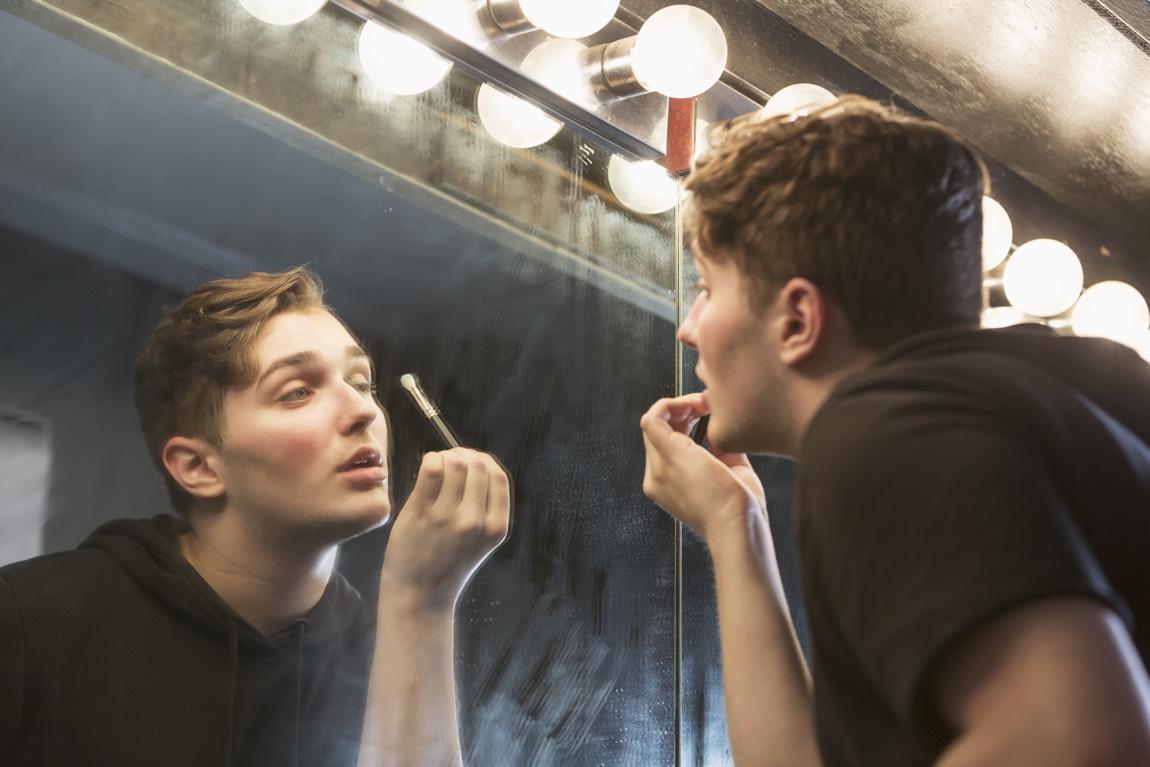 Junger Mann schaut in einen Spiegel und schminkt sich.