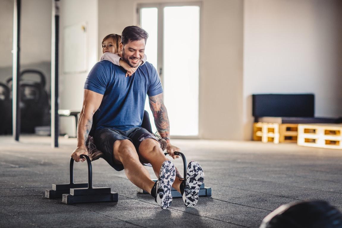 Junger muskulöser Vater trainiert mit Hanteln, während er seine Tochter Huckepack hält.