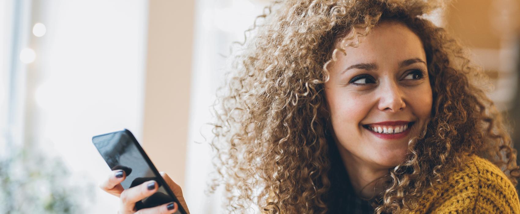 Junge Frau mit lockigen Haaren und gelbem Pullover blickt über die Schulter.