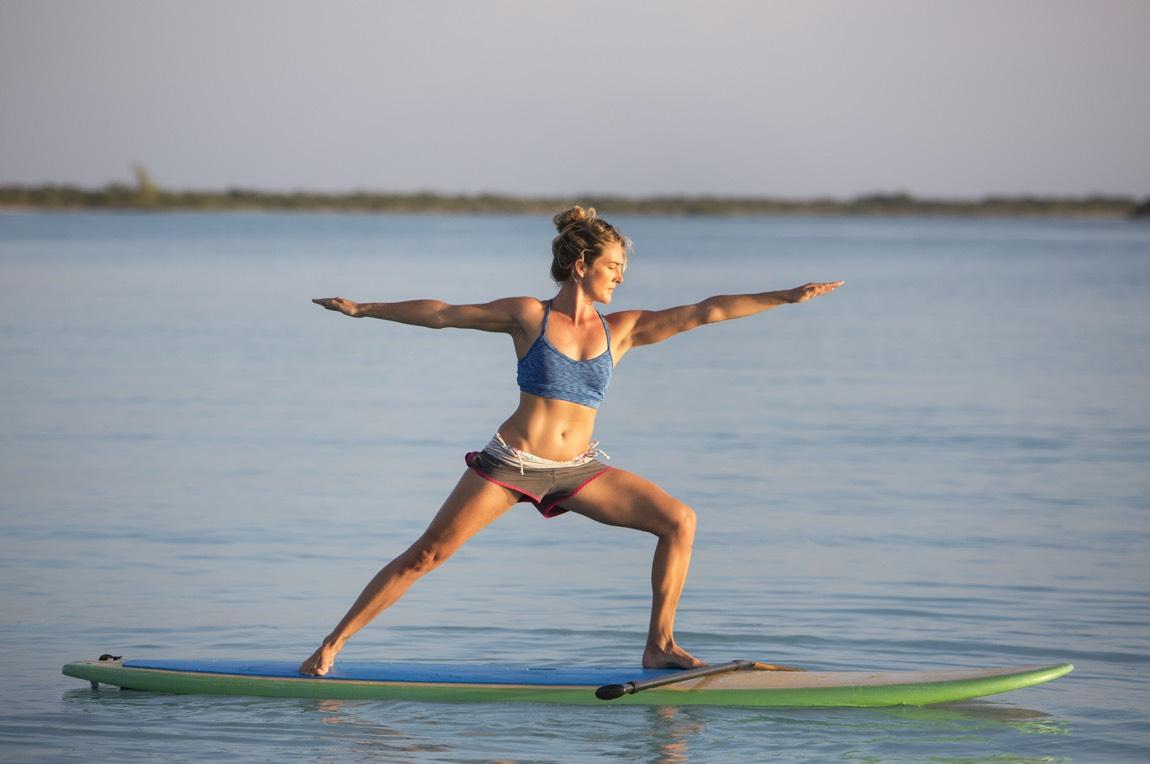 Junge Frau beim Yoga auf dem Paddling Board.