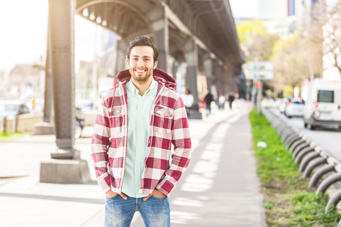 Junger Mann in karierter Jacke steht unter einer Brücke in der Stadt.