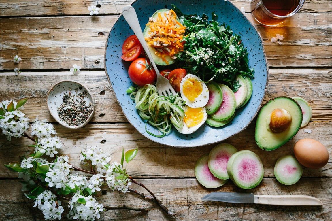 Bunter Salat, daneben Eier und Avocado auf einem rustikalen Holztisch angerichtet. Foto von Brooke Lark.