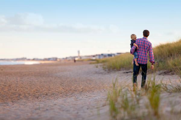 Vater mit Kind auf dem Arm am Strand