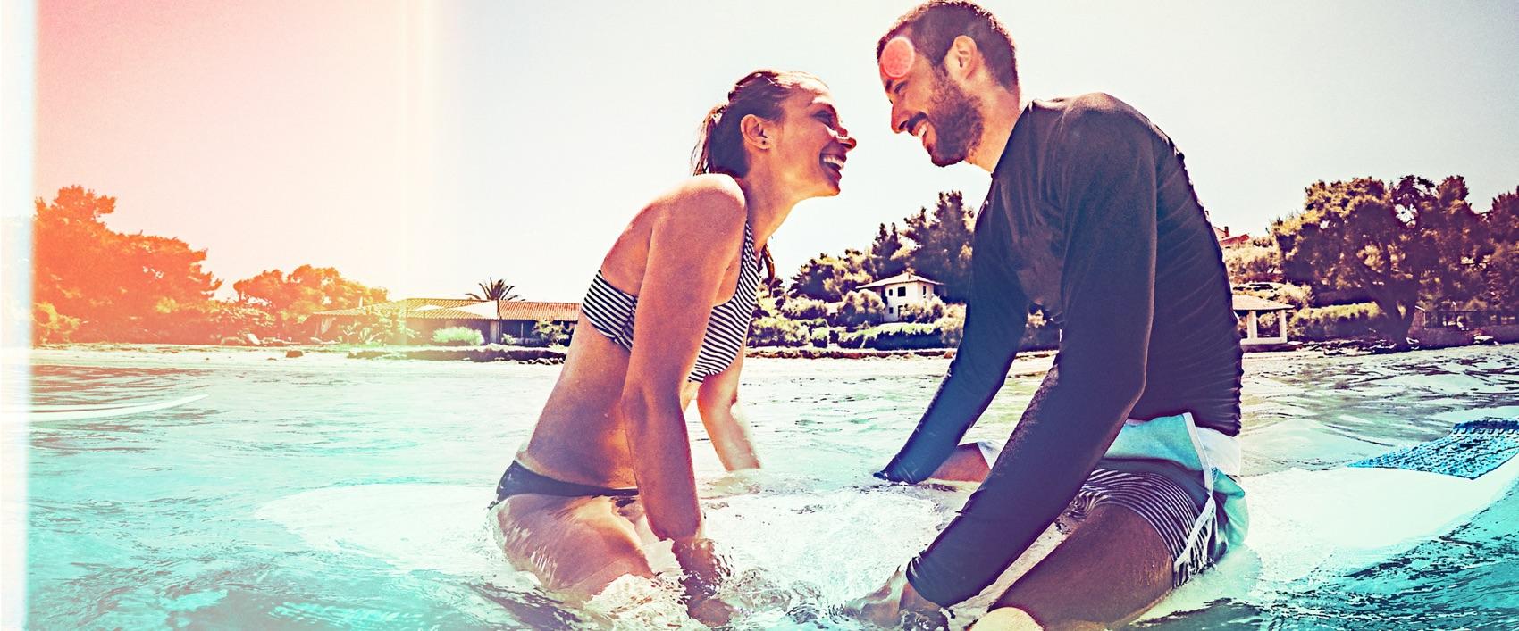 Verliebtes Surfer-Paar auf einem Surfbrett im Meer.