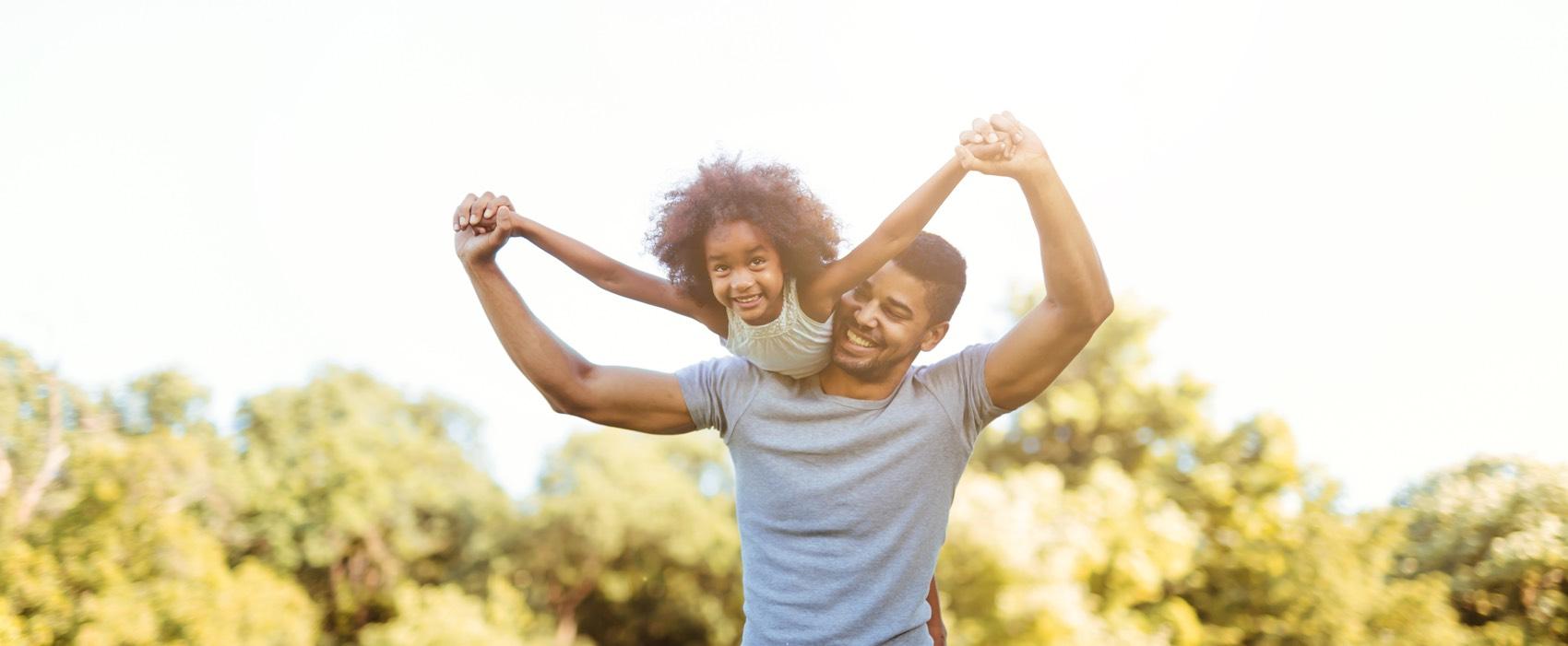 Junger Vater tobt mit seiner Tochter, die er auf seiner Schulter trägt.
