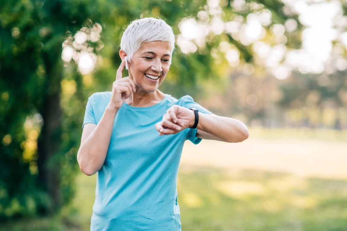 Sportliche Seniorin beim Sport schaut auf ihre Smartwatch.