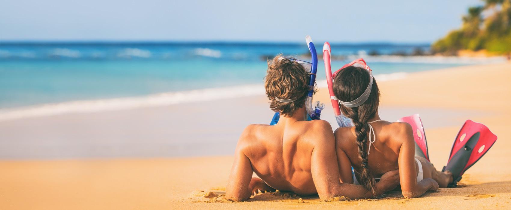 Paar mit Taucherbrille und Flossen am Strand von hinten.