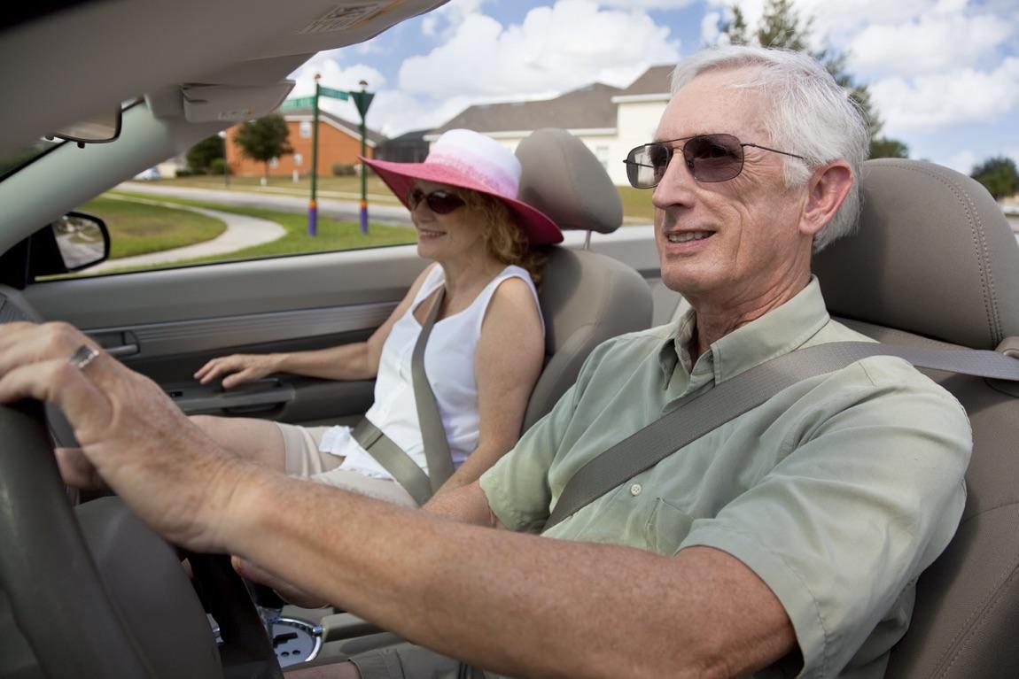 Älteres Ehepaar sitzt im Cabrio.