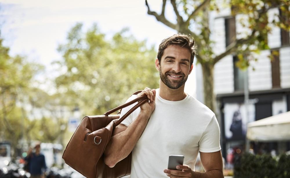 Junger Mann in weißem T-Shirt mit Sporttasche und Handy blickt in die Kamera.