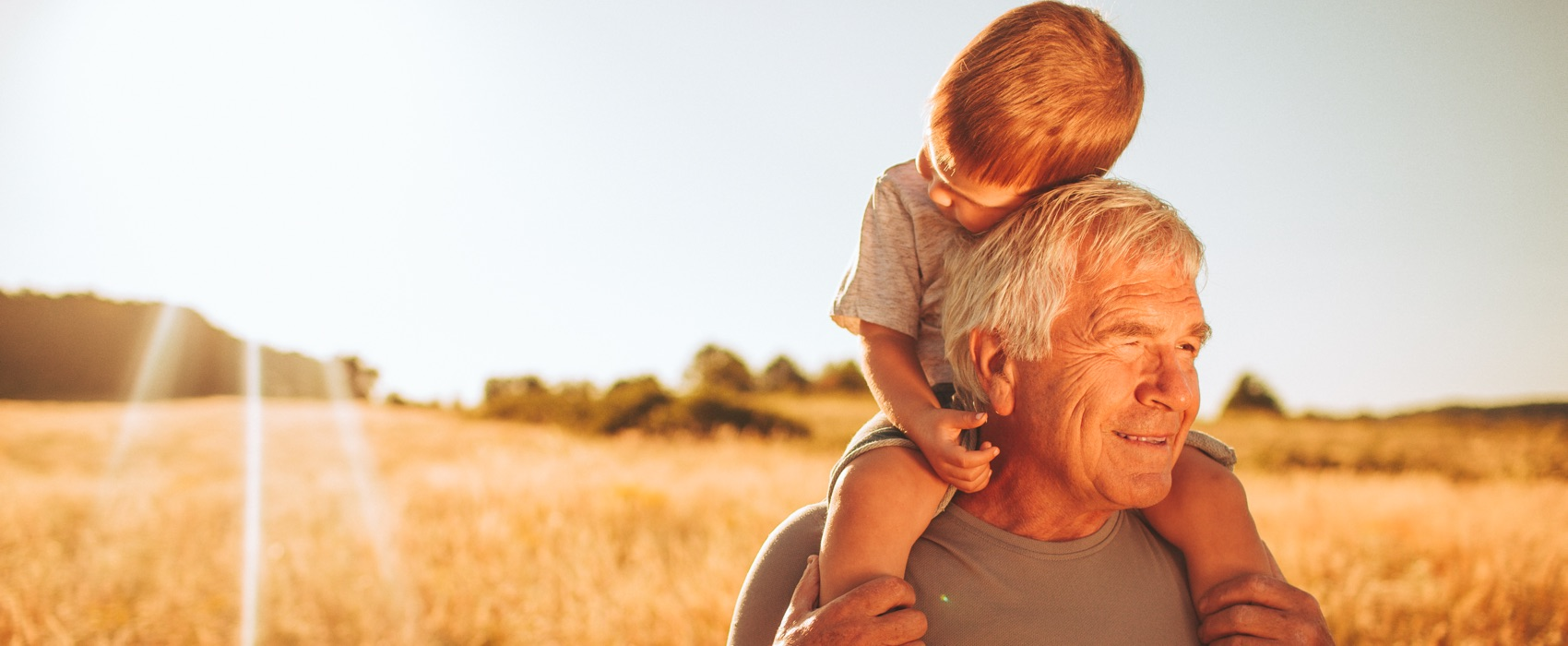 Großvater trägt Enkel auf seinen Schultern.