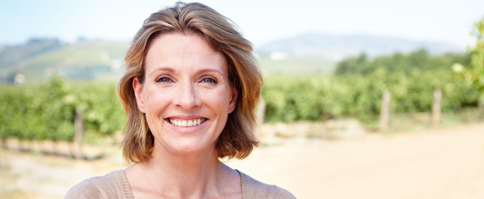 Frau mittleren Alters an einem Weinberg blickt lächelnd in die Kamera.