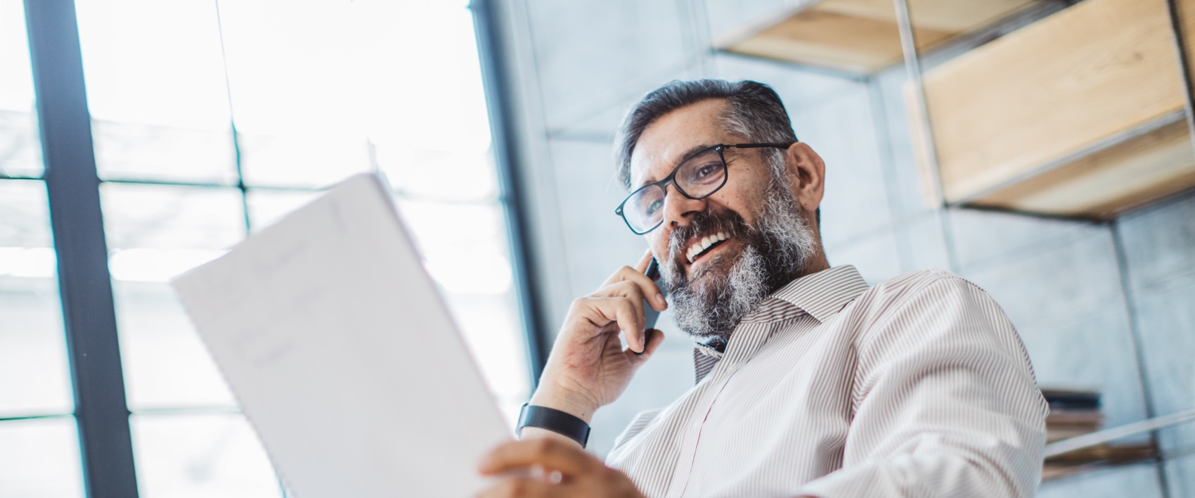 Mann im Büro mit Brille schaut sich Unterlagen an, während der telefoniert.