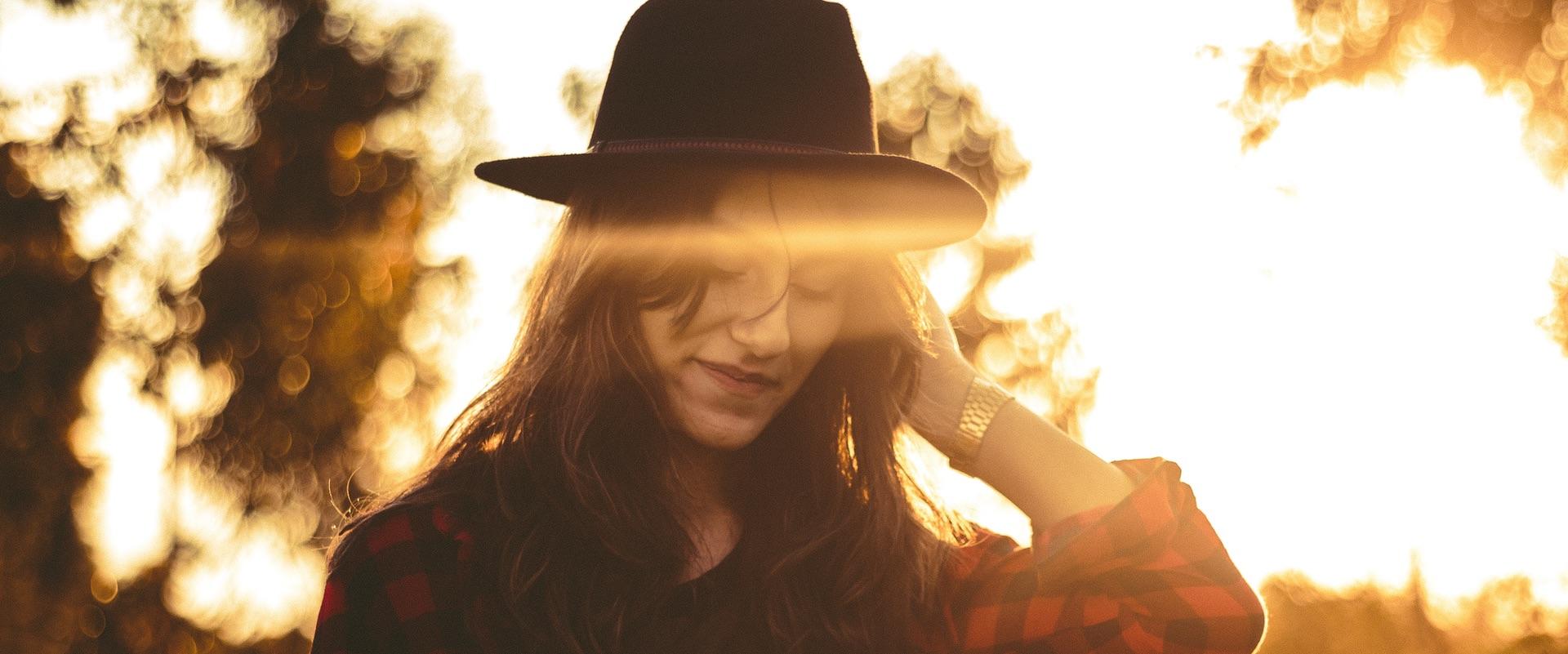 Brillenunabhängigkeit bei Kurzsichtigkeit: Junge Frau mit Hut im Sonnenlicht.
