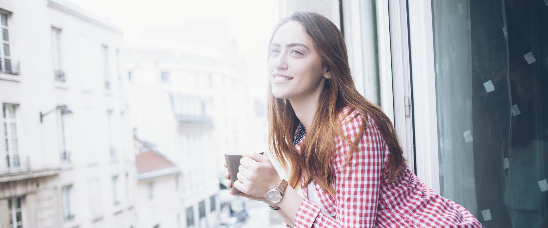 Junge Frau mit einer Tasse Kaffee blickt entspannt aus dem Fenster.