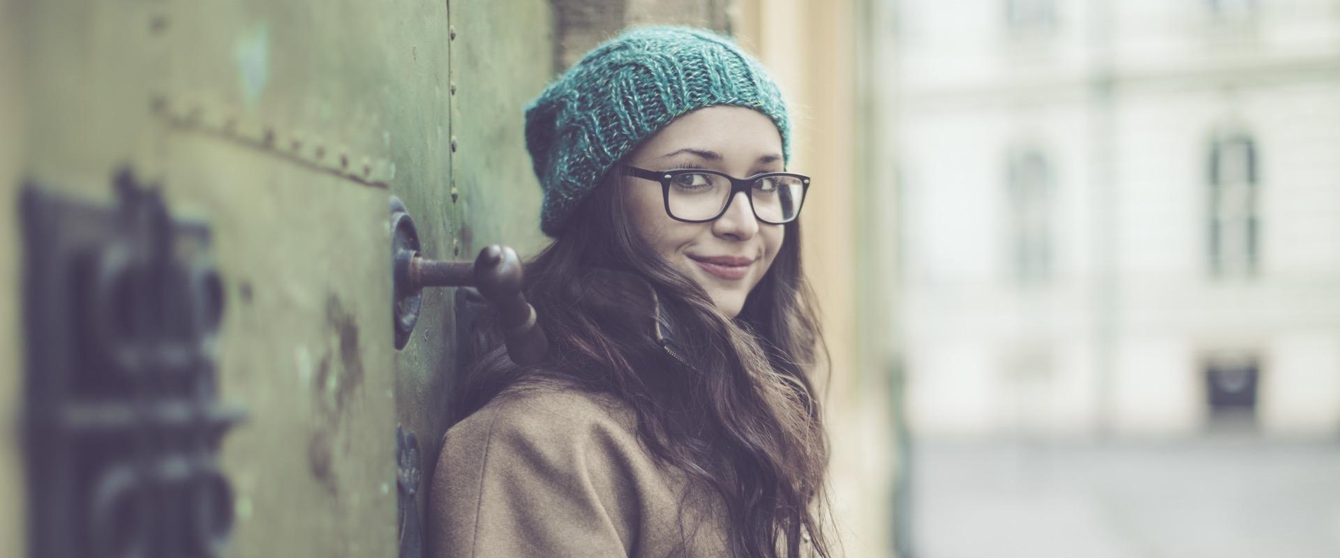 Junge Frau mit Mütze und Brille lehnt an einer Häuserwand und schaut in die Kamera.