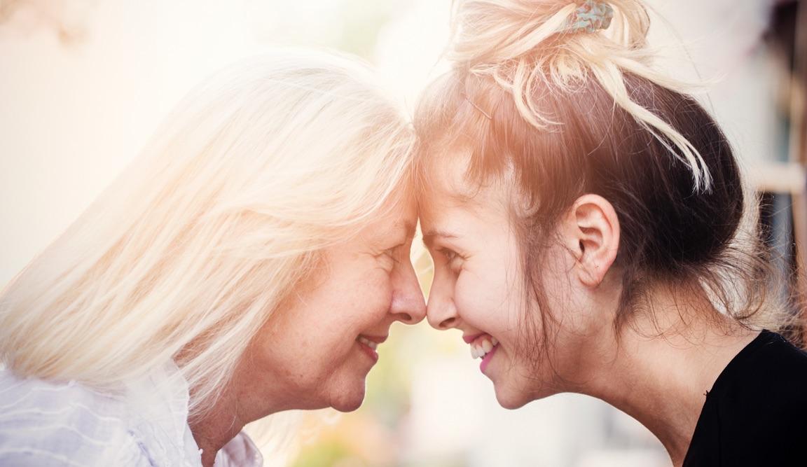 Mutter und Tochter, Stirn an Stirn, schauen sich in die Augen.