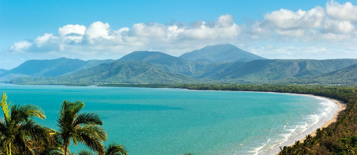 Strand von Port Douglas, Australien mit Palmen, im Hintergrund Berge