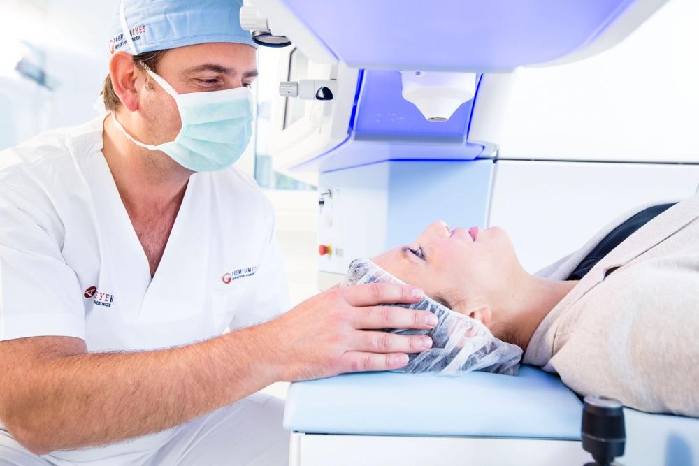 Dr. Breyer mit einer Patientin, die unter dem Laser liegt, er legt seine Hände beruhigend an ihren Kopf.