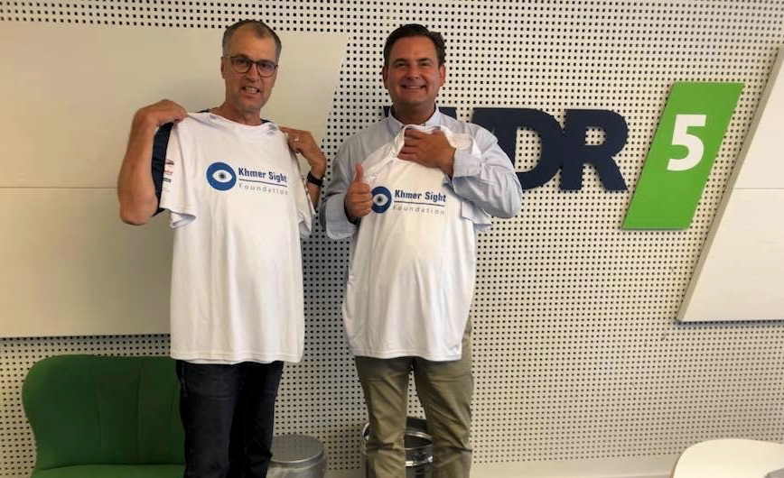 WDR-Redakteur Thomas Koch (links) und Detlev Breyer präsentieren T-Shirts der Khmer Sight Foundation.