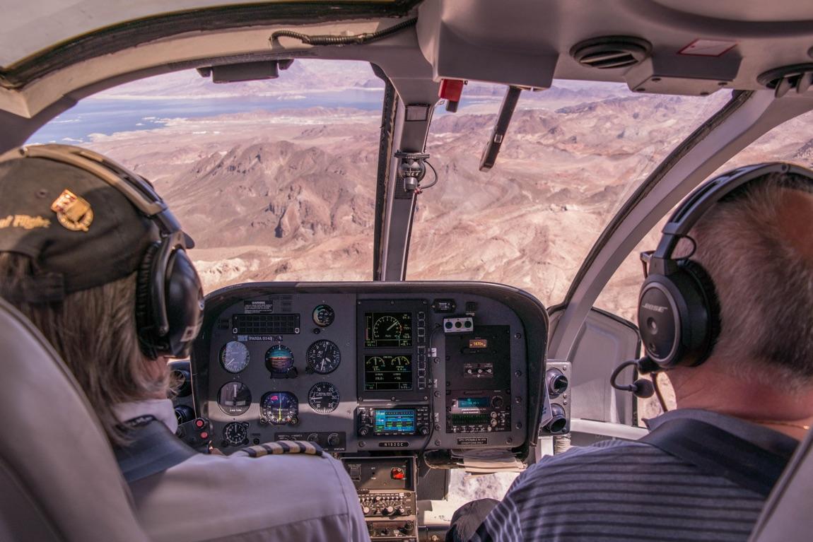 Blick von hinten ins Cockpit mit zwei Piloten beim Landeanflug über einer bergigen Küstenregion.