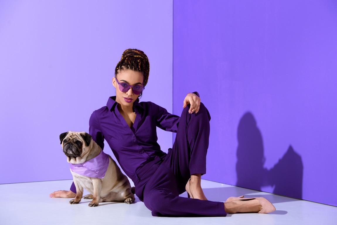 Junge Frau in Violett gekleidet mit violetter Sonnenbrille sitzt vor violetter Wand neben einem Mops mit violettem Halstuch.
