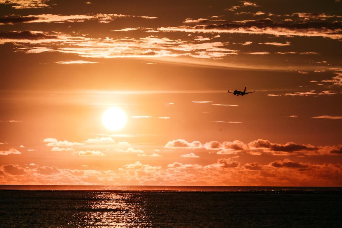 Sonnenuntergang über dem Meer, am Himmel ist ein Flugzeut zu sehen.