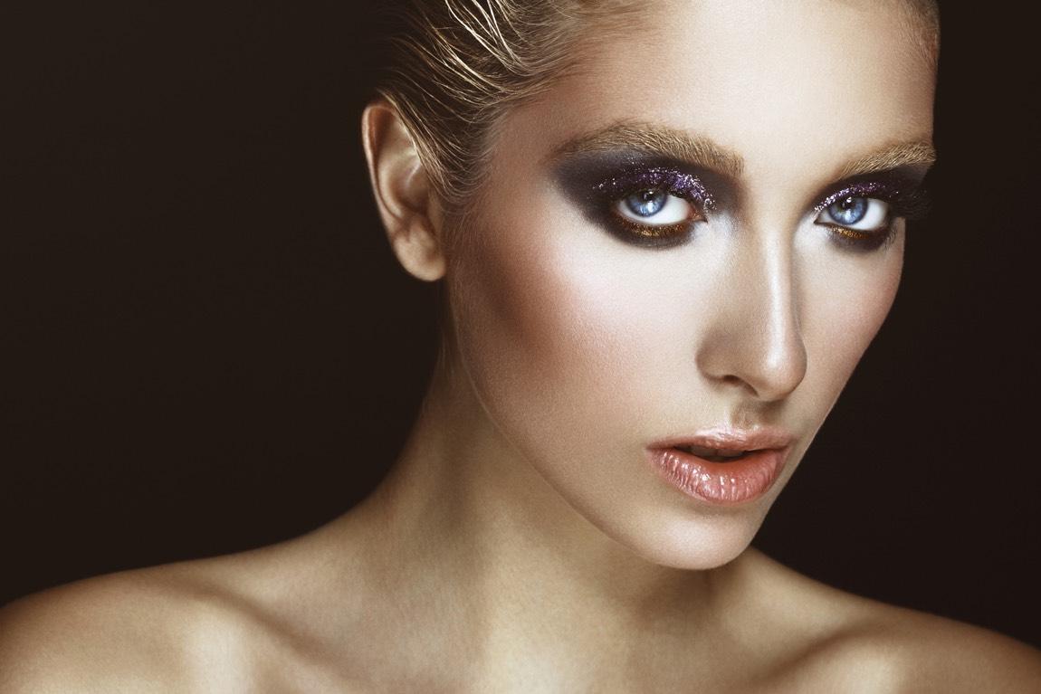 Junge Frau mit Glitzer-Make-up vor allem im Bereich der Augenpartie.