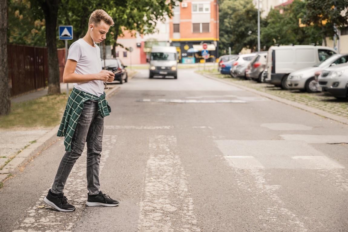 Obwohl er sich auf sein Smartphone konzentriert, wird dieser junge Mann das sich nähernde Fahrzeug in der Peripherie wahrnehmen. © Dobrila Vignjevic