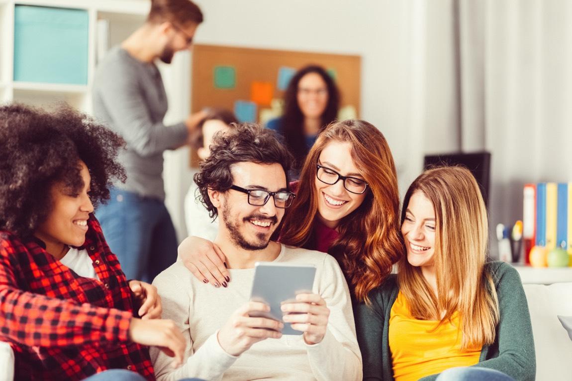 Junge Studenten, zwei davon mit Brille, sind in einem Seminarraum und schauen gemeinsam in ein Tablet.