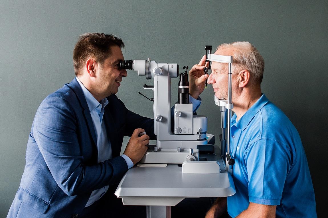 Augenarzt Dr. Kaymak bei der Behandlung eines Patienten.