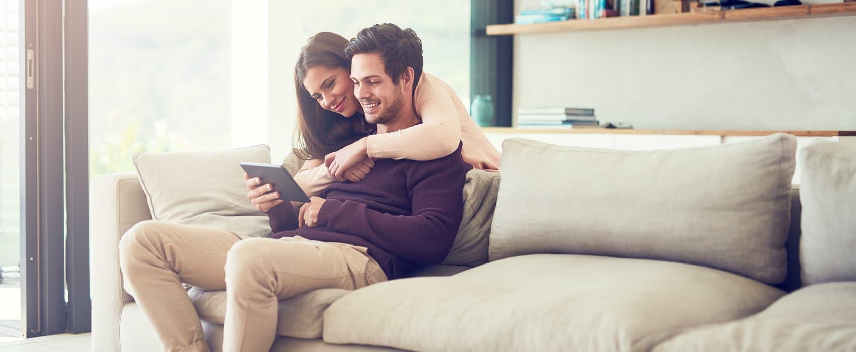 Junges Paar sitzt zuhause auf dem Sofa und schaut in ein iPad.