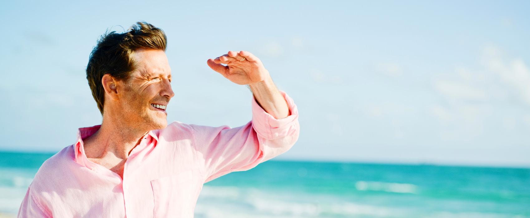 Mann mittleren Alters am Meer, hält seine Hand hoch, um sich vor der Sonne zu schützen.
