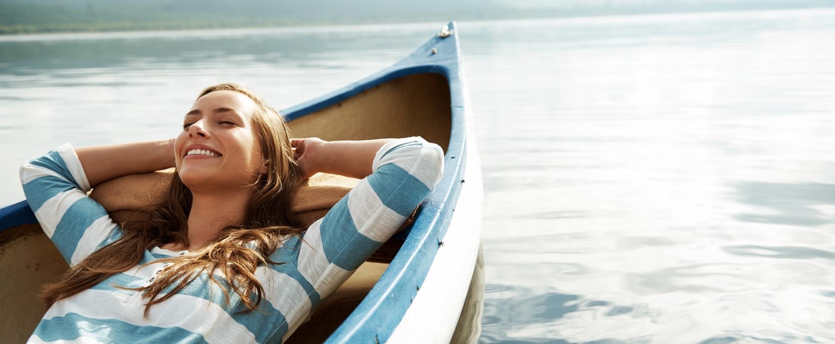 Junge Frau liegt lächelnd in einem Boot, das auf dem Wasser schwimmt.