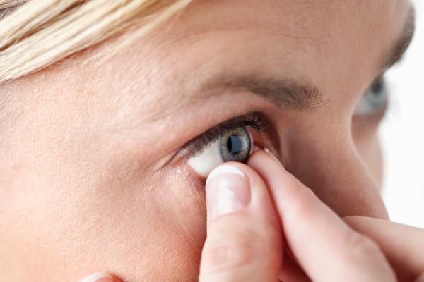 Bild einer Frau, die sich grade die Kontaktlinse eingesetzt hat und die Finger noch am Auge hat.