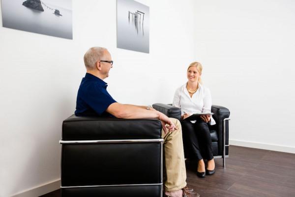 Bild von einer Mitarbeiterin und einem Patienten bei einem Gespräch über alle Schritte der Operation und was zu beachten ist.