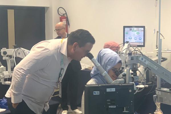 Dr. Breyer schaut durch ein zweites Operationsmikroskop einer Augenchirurgin bei einer Operation zu.