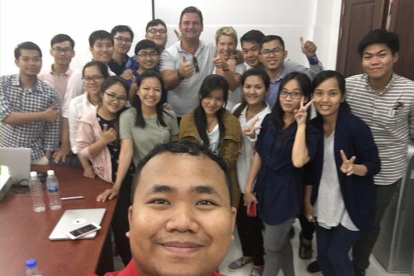 Selfie eines Mitarbeiters der Klinik in Phnom Penh mit dem Team und Ehepaar Breyer im Hintergrund.